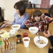 Stock Photo: Parents Taking Away Gadgets From Children Whilst Eating Breakfas