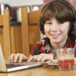 Stock Photo: Boy Using Laptop Whilst Eating Breakfast