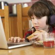 Boy Using Laptop Whilst Eating Breakfast - 
