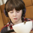Boy Using Tablet Computer Whilst Eating Breakfast - Foto Stock