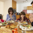 Family Saying Grace Before Eating Lunch Together In Kitchen — Stok fotoğraf