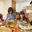 Family Saying Grace Before Eating Lunch Together In Kitchen — Stockfoto