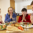 Stock Photo: Teenage Family Saying Grace Before Eating Lunch Together In Kitc