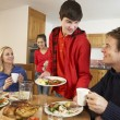 Helpful Teenage Children Serving Food To Parents In Kitchen — Stock Photo
