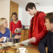 Unhelpful Teenage Clearing Up After Family Meal In Kitchen — Stock Photo #11893355