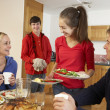 Stock Photo: Helpful Teenage Children Serving Food To Parents In Kitchen
