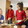 Foto Stock: Unhelpful Teenage Clearing Up After Family Meal In Kitchen