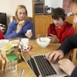 Teenage Family Using Gadgets Whilst Eating Breakfast Together In - Foto de Stock