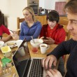 Teenage Family Using Gadgets Whilst Eating Breakfast Together In — Stock Photo #11893372