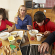 Teenage Family Using Gadgets Whilst Eating Breakfast Together In — ストック写真