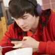 Teenage Boy Listening To MP3 Player Whilst Eating Breakfast — Stock fotografie