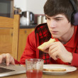 Teenage Boy Using Laptop Whilst Eating Breakfast — Stock Photo