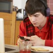 Teenage Boy Using Laptop And Listening To MP3 Player Whilst Eati — Stock Photo