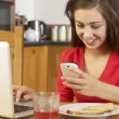 Stock Photo: Teenage Girl Using Laptop And Mobile Phone Whilst Eating Breakfa