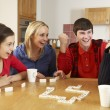 Family Playing Dominoes In Kitchen - Stockfoto