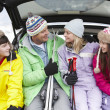 Stock Photo: Teenage Family Sitting In Boot Of Car With Skis