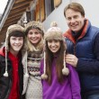 Portrait Of Family Standing Outside Chalet On Ski Holiday — Stock Photo #11893457