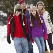 Teenage Family Walking Along Snowy Street In Ski Resort - Foto de Stock  