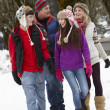 Royalty-Free Stock Photo: Teenage Family Walking Along Snowy Street In Ski Resort