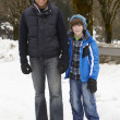 Stock Photo: Father And Son Walking Along Snowy Street In Ski Resort
