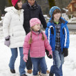 Family Walking Along Snowy Street In Ski Resort - Foto Stock