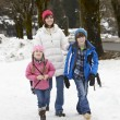 Mother Walking Two Children To School Along Snowy Street In Ski — Stock Photo