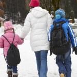 Mother Walking Two Children To School Along Snowy Street In Ski — Stock Photo