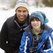 Portrait Of Father And Son Wearing Winter Clothes In Snowy Lands - Foto Stock