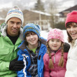 Portrait Of Family Wearing Winter Clothes In Snowy Landscape - Stockfoto
