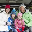 Family Sitting In Boot Of Car Wearing Winter Clothes - Stockfoto