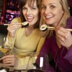 Two Women Enjoying Sushi In Restaurant — Stock Photo #11893635