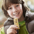 Boy Eating Healthy Snack Bar Wearing Winter Clothes — Stock Photo