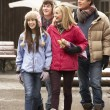Teenage Family Walking Along Snowy Town Street In Ski Resort — Stockfoto