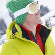 Young Man On Ski Holiday In Mountains - Stock Photo