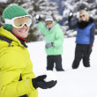 Group Of Young Friends Having Snowball Fight On Ski Holiday In M - Foto Stock