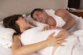 Pregnant woman and husband in bed — Stock Photo