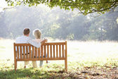 Senior couple sitting outdoors — Foto de Stock