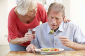 Senior woman looking after sick husband — Stock Photo