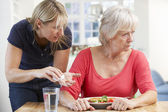 Older woman refusing medication at home — Stock Photo