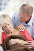Senior man looking after sick wife — Stock Photo