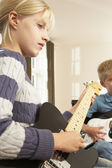 Boy and girl playing electric guitars at home — Stock Photo