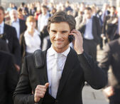 Male commuter in crowd using phone — Stock Photo