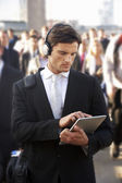 Male commuter in crowd with tablet and headphones — Stok fotoğraf