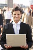 Mannelijke commuter in menigte met behulp van laptop — Stockfoto