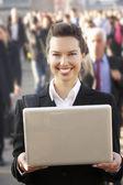Vrouwelijke forensen in menigte met behulp van laptop — Stockfoto