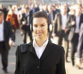 Viajante de bilhete mensal feminino na multidão usando fones de ouvido — Foto Stock