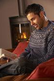 Hombre envejecido medio relajante con libro de acogedora chimenea — Foto de Stock