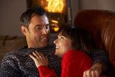 Meio envelhecido casal conversando no sofá por uma acolhedora lareira — Foto Stock