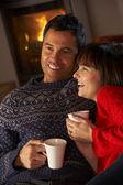 Meio envelhecido casal sentado no sofá pelo log acolhedor de fogo quente dri — Foto Stock