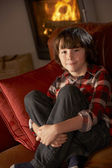 Young Boy Sitting On Sofa By Cosy Log Fire — Stock Photo